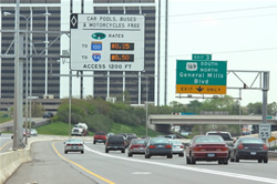"Picture of MnPass facility in Minnesota stating ""Car pools, buses and motorcycles (are) Free"" while displaying toll rates for non-exempt vehicles."